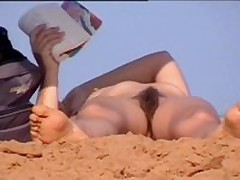 cute woman with hairy pussy sunbathing at naked beach