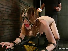 Cici Rhodes likes the dungeon. Belted to a board, tied and gagged the brunette hair receives a punishment with hot wax and spanking. Her master removes a metal plug from her ass, then re-inserts it, attaching a rope from it to her head. A vibrator runs over her pussy, making her want to cum, but can't yet.
