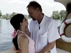 Girl in a pink dress sucks on a boat